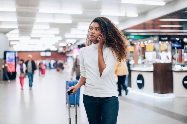 Młoda kobieta na lotnisku z torbą na kółkach, rozmawia przez telefon.