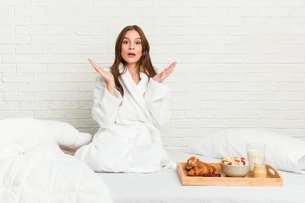 Młoda kobieta na łóżku zaskoczona i zszokowana