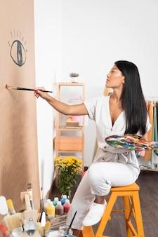 Młoda kobieta na malowanie krzesła