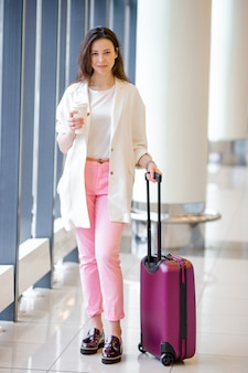 Młoda kobieta na międzynarodowym lotnisku, chodzenie z bagażem i kawą na wynos