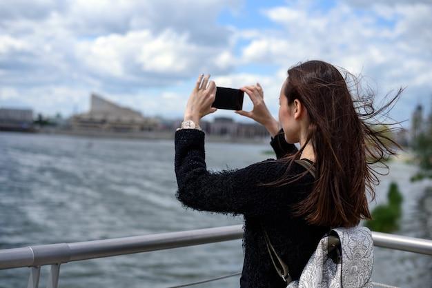 Młoda kobieta na nabrzeżu robienia zdjęć krajobrazu miasta