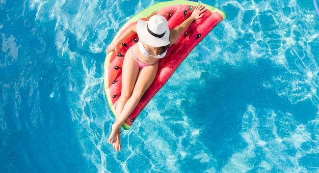 Młoda kobieta na nadmuchiwanej macie przy basenie