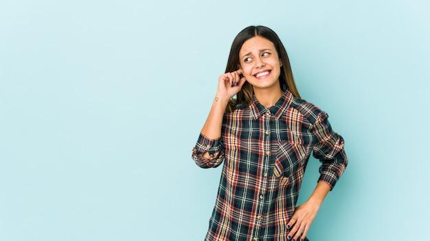 Młoda kobieta na niebieską ścianę obejmujące ucho ręką