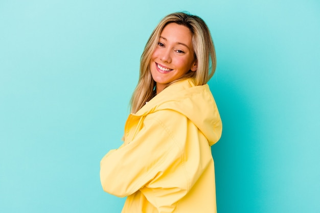 Młoda kobieta na niebieskiej ścianie szczęśliwa, uśmiechnięta i wesoła