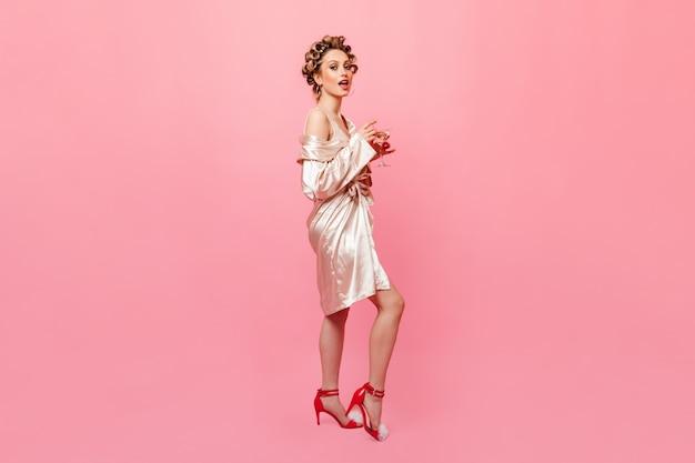 Młoda kobieta na obcasach, ubrana w szlafrok patrzy z przodu i trzyma kieliszek martini