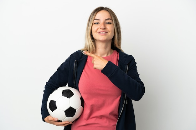 Młoda kobieta na odosobnionym białym tle z piłką nożną i wskazującą na bok