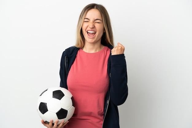 Młoda kobieta na odosobnionym białym tle z piłką nożną świętującą zwycięstwo