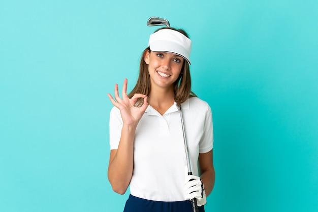Młoda kobieta na odosobnionym niebieskim tle, grając w golfa, robiąc znak ok