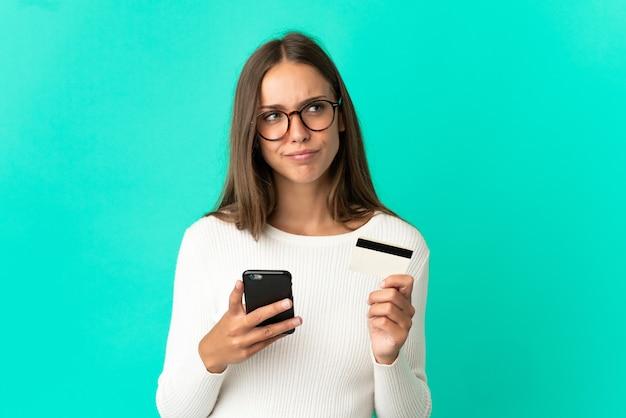 Młoda kobieta na odosobnionym niebieskim tle kupując telefon komórkowy za pomocą karty kredytowej podczas myślenia