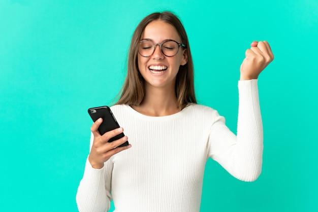 Młoda kobieta na odosobnionym niebieskim tle, używająca telefonu komórkowego i wykonująca gest zwycięstwa