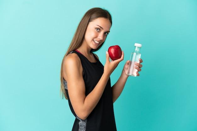 Młoda kobieta na odosobnionym niebieskim tle z jabłkiem i butelką wody