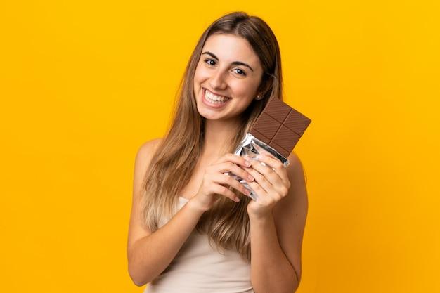 Młoda kobieta na odosobnionym żółtym biorąc czekoladową tabletkę i szczęśliwa