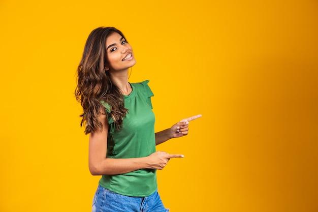 Młoda kobieta na odosobnionym żółtym tle, wskazując palcem w bok