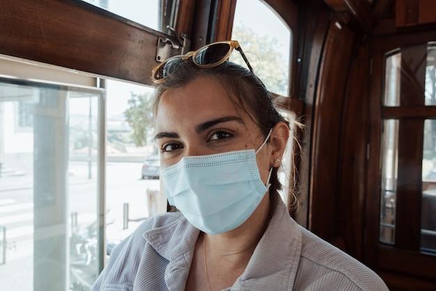 Młoda kobieta na okularach przeciwsłonecznych i masce na twarz w starym pociągu w porto, uśmiechając się do kamery na niezależnych ubraniach, podróżach i koncepcji nowych doświadczeń