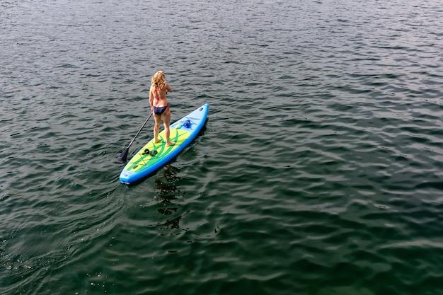 Młoda kobieta na paddle desce przy jeziorem. łyk. widok z tyłu.