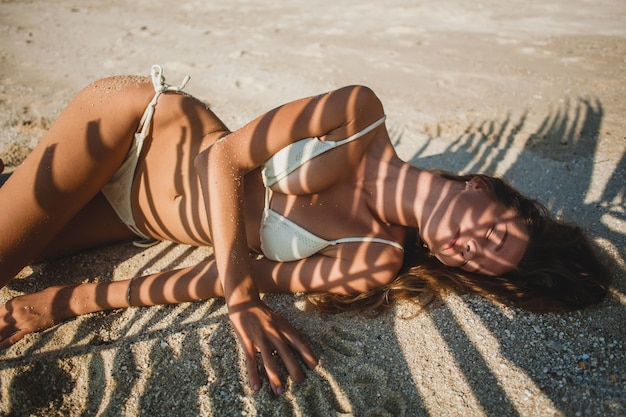 Młoda kobieta na piaszczystej plaży pod liśćmi palmy