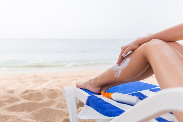 Młoda kobieta na plaży i chroni skórę, stosując krem z filtrem przeciwsłonecznym na nogę.