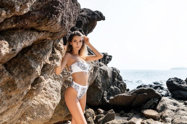 Młoda kobieta na plaży. portret dziewczynki w białym bikini. piękne skały tropikalne tło