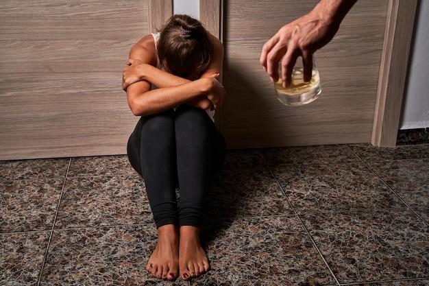 Młoda kobieta na podłodze podczas wykorzystywania przez swojego partnera. pojęcie znęcania się, przemocy i znęcania się nad kobietami