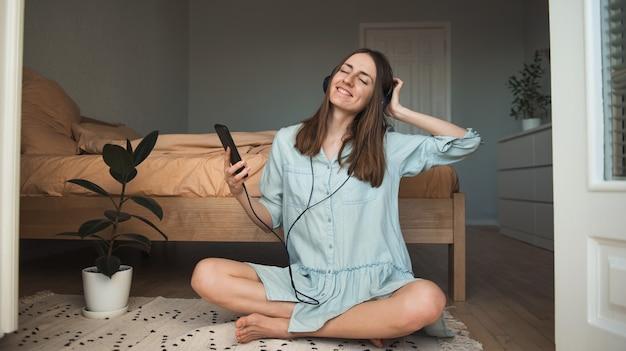 Młoda kobieta na podłodze, słuchając muzyki z zamkniętymi oczami