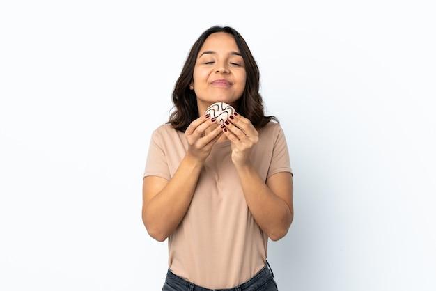 Młoda kobieta na pojedyncze białe tło trzyma pączek