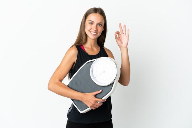 Młoda kobieta na pojedyncze białym tle trzyma maszynę do ważenia i robi znak ok