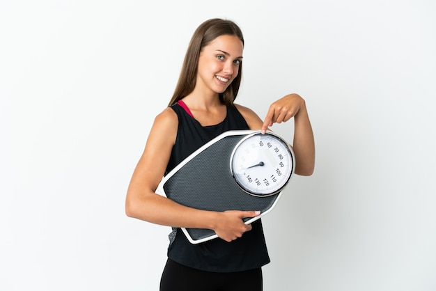 Młoda kobieta na pojedyncze białym tle trzyma wagę i wskazuje ją