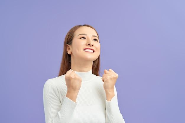 Młoda kobieta na pojedyncze fioletowe ściany świętuje zwycięstwo