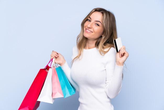 Młoda kobieta na pojedyncze niebieskie ściany gospodarstwa torby na zakupy i karty kredytowej