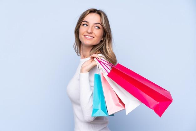 Młoda kobieta na pojedyncze niebieskie ściany gospodarstwa torby na zakupy i patrząc wstecz