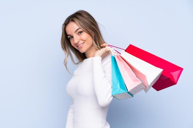 Młoda kobieta na pojedyncze niebieskie ściany gospodarstwa torby na zakupy i uśmiechnięte
