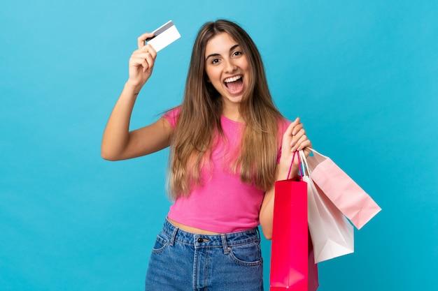 Młoda kobieta na pojedyncze niebieskie ściany gospodarstwa torby na zakupy i zaskoczony