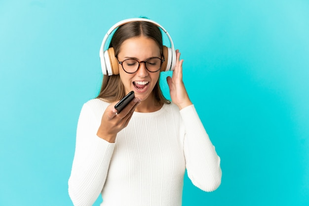 Młoda kobieta na pojedyncze niebieskie tło słuchania muzyki z telefonu komórkowego i śpiewu