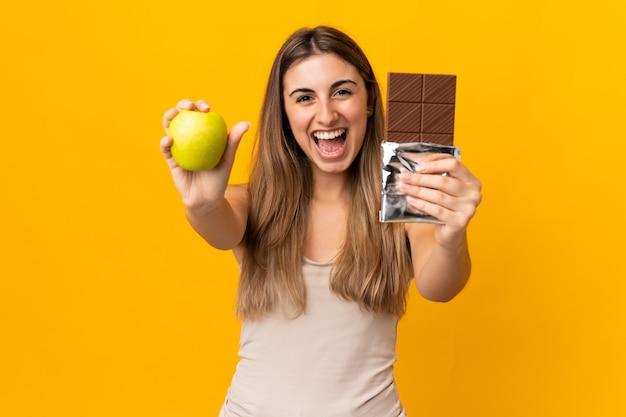 Młoda kobieta na pojedyncze żółte, biorąc tabletkę czekolady w jednej ręce i jabłko w drugiej