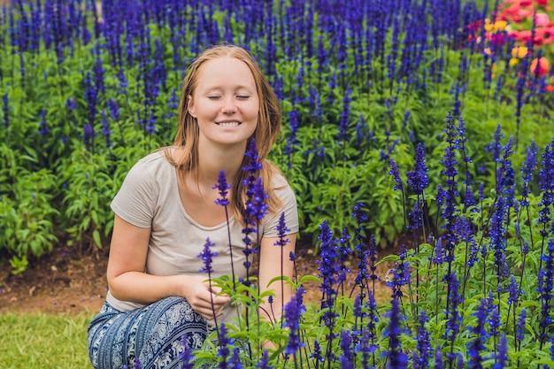 Młoda kobieta na powierzchni kwitnących w ogrodzie kwiatów blue salvia farinacea