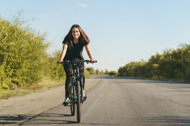 Młoda kobieta na rowerze, jazda na drogach