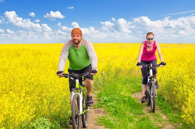 Młoda kobieta na rowerze w żółtym polu kwiatów