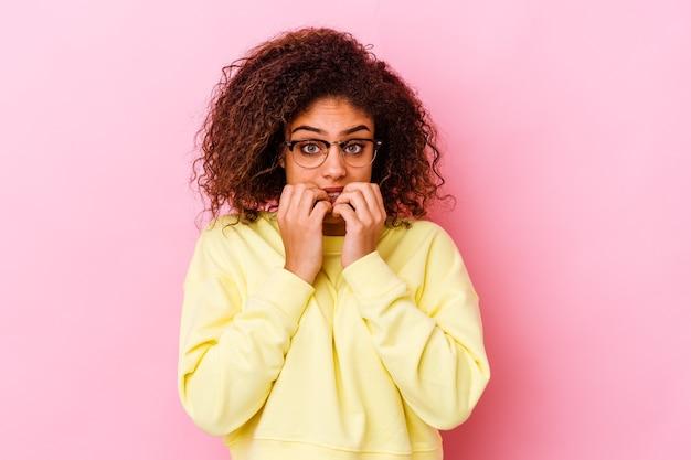 Młoda kobieta na różowej ścianie gryzie paznokcie, nerwowa i bardzo niespokojna