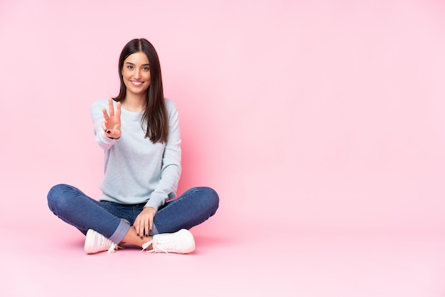 Młoda kobieta na różowym szczęśliwym i liczący trzy z palcami