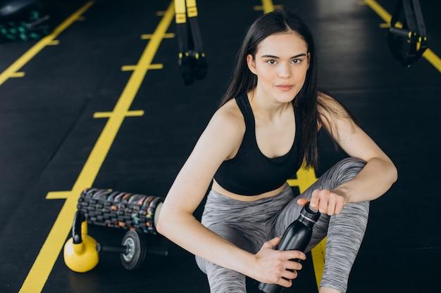 Młoda kobieta na siłowni, pijąca wodę