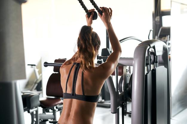 Młoda kobieta na siłowni ściska ręce na specjalnym symulatorze
