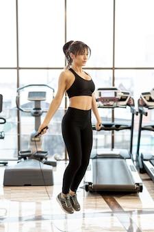 Młoda kobieta na siłowni treningu z skakanka