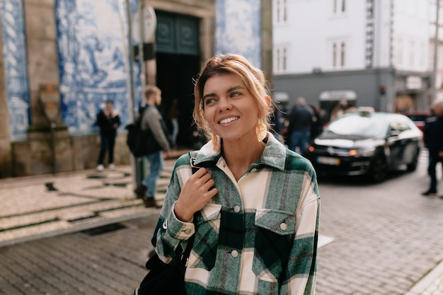 Młoda kobieta na sobie dżinsową koszulę spaceru na ulicy miasta
