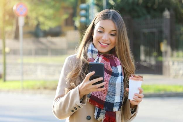 Młoda kobieta na sobie płaszcz i szalik spaceru na ulicy