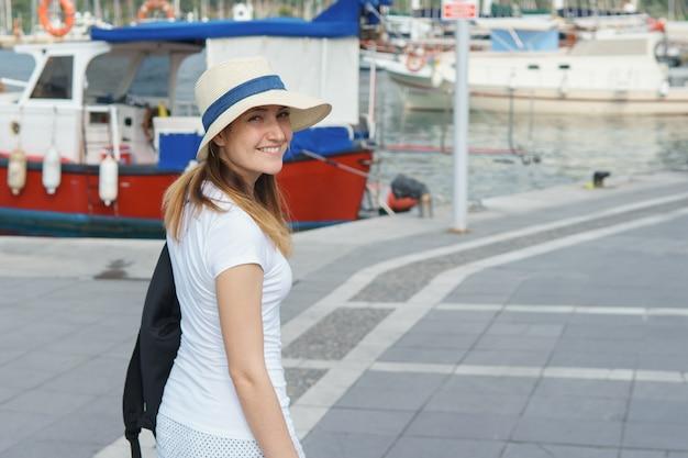 Młoda kobieta na spacerze wzdłuż nabrzeża do molo w słoneczny dzień, kopia przestrzeń