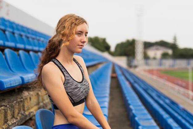 Młoda kobieta na stadionie siedzi