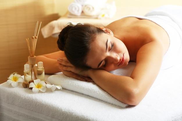 Młoda kobieta na stole do masażu w salonie piękności spa