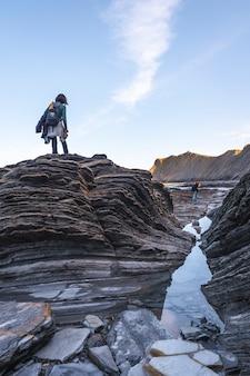 Młoda kobieta na szczycie kamieni w geoparku wybrzeża sakoneta