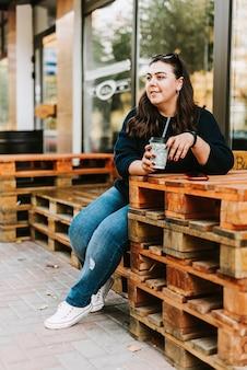 Młoda kobieta na tarasie picia kawy
