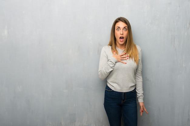 Młoda kobieta na teksturowanej ścianie zaskoczony i zszokowany, patrząc w prawo